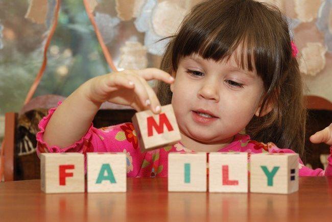 дівчинка складає кубики з англійськими літерами