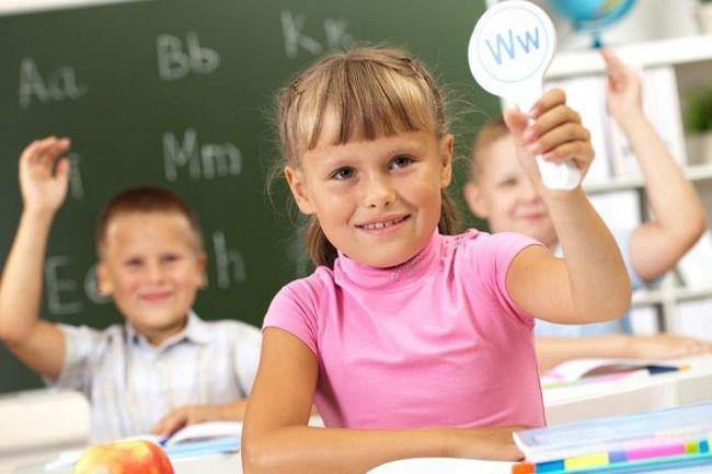дівчинка показує іноземну букву